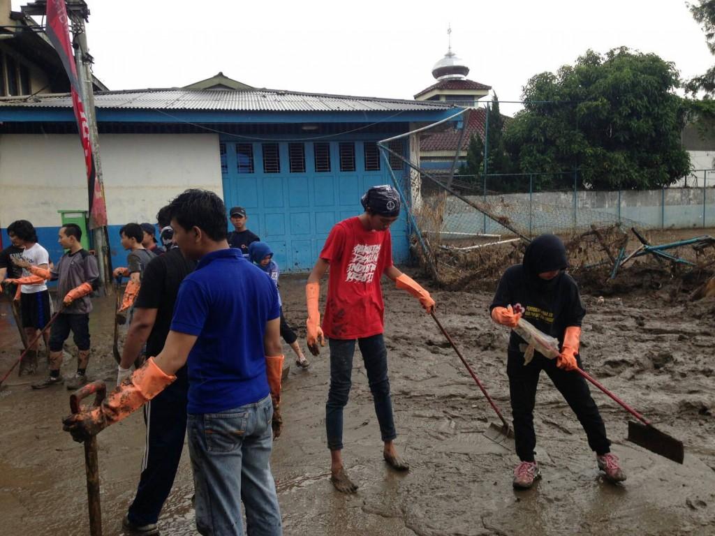 Mahasiswa Universitas Esa Unggul membersihkan lumpur setinggi 30 cm
